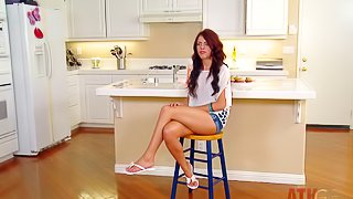 Adorable long haired brunette teen with small boobs and long sexy legs in hot pants and shirt answer questions at her first interview while sitting on bar chair in the kitchen