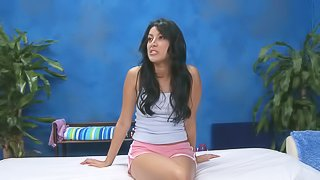 Kimberly with long black hair gives interview on camera in the massage studio before stripping for massage. She wears pink shorts and shows off her nice legs