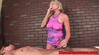Mature masseuse smokes while rubbing cock